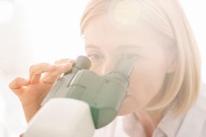 kobieta przegląda preparat pod mikroskopem